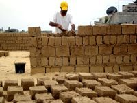 Nidal Eid builds his home with mud bricks