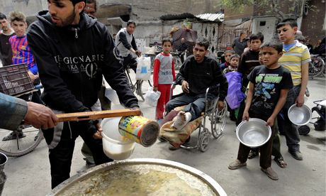 Volunteers distribute free meals to residents at the Palestinian refugee camp of Yarmouk. Photograph: Reuters