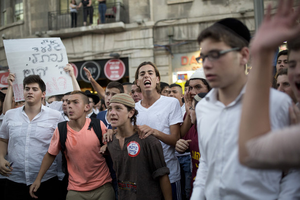"At a right-wing protest in Jerusalem a sign reads ""May God avenge their blood"" and a youth wears a sticker stating ""Kahane was right,"" referring to the Brooklyn-born violent settler movement leader, 1 July. (Tali Mayer / ActiveStills)"
