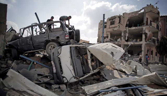 Palestinians search destroyed cars in Rafah's district of Shawkah in the southern Gaza Strip. August 5, 2014. Photo by AP
