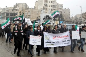 Protesters carry banners and opposition flags as they march in Aleppo, Syria, asking for the release of prisoners held in government jails and the lifting of the siege on besieged areas.